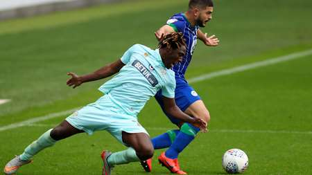 Osman Kakay is beaten to the punch by Wigan captain Sam Morsy